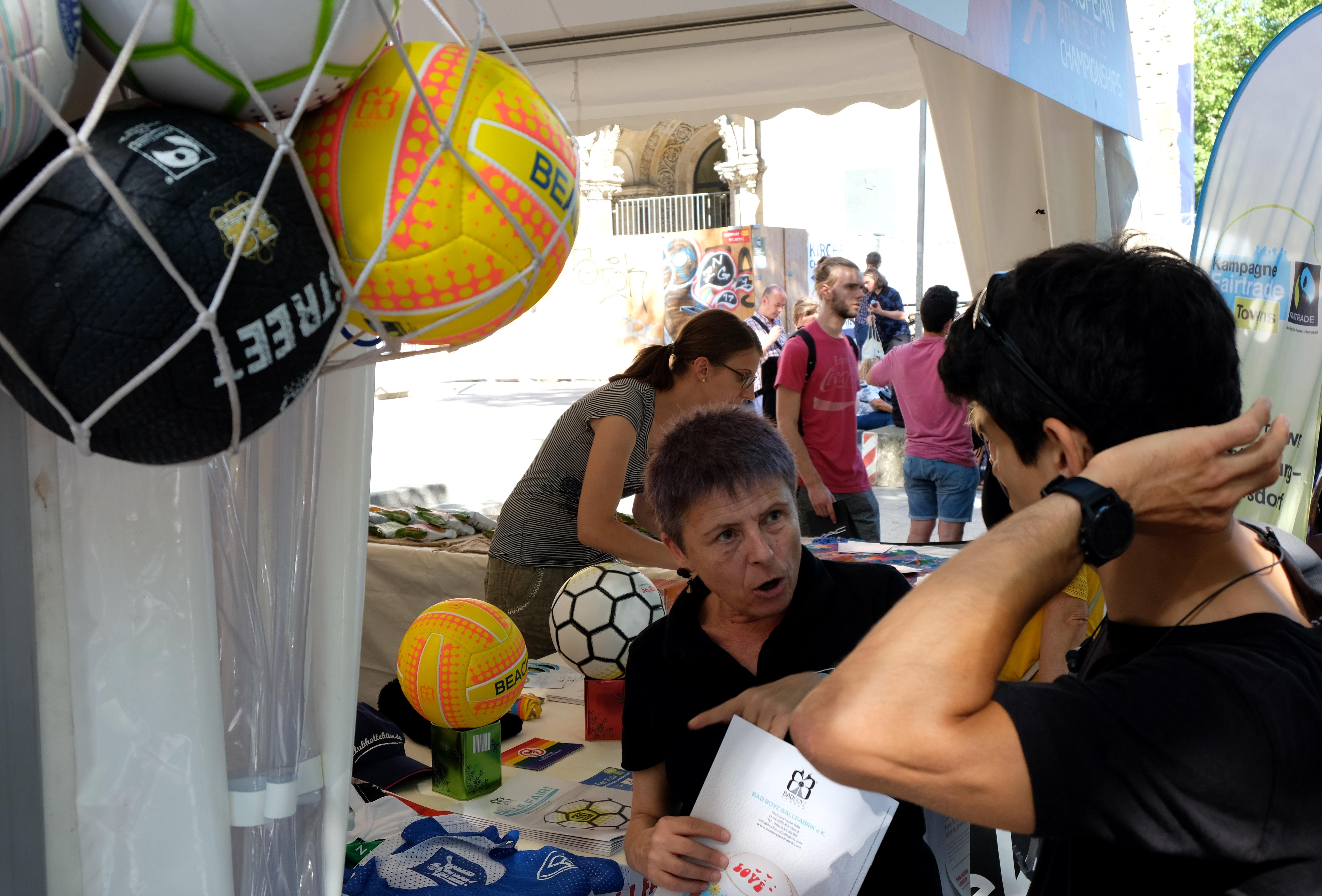 Marlene Cieschinger erklärt einem Besucher die Vorteile fair gehandelter Fußbälle