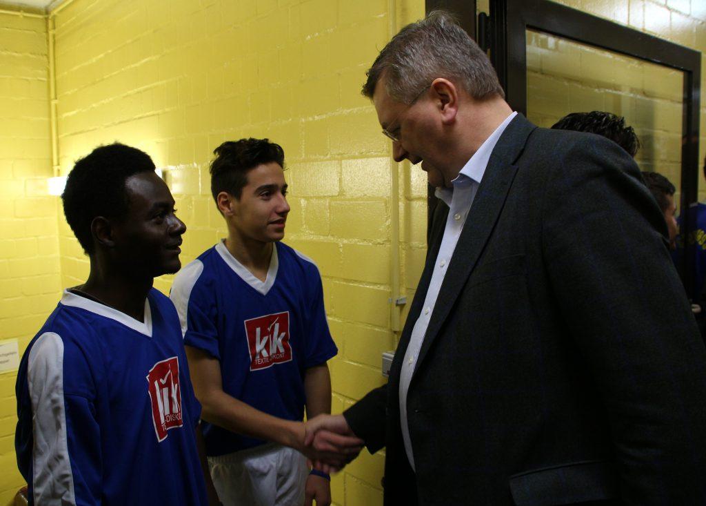 Reinhard Grindel bei der Begrüßung einiger Jugendspieler aus einer Mannschaft von GeflüchtetenDezember 2015